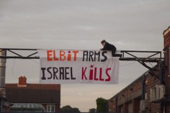 Protester hangs _Elbit Arms, Israel Kills_ at shutdown Elbit factory in Birmingham. The factory produces drone engines which are exported to Israel and used over Gaza copy